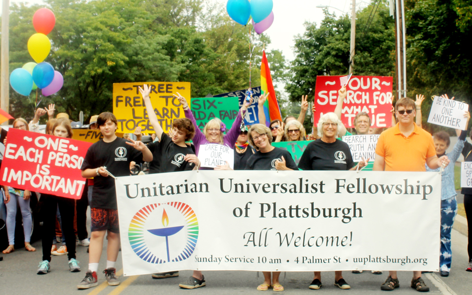 Members of the congregation pose with welcoming banner.